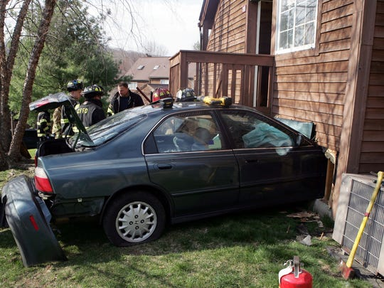Brewster and Croton Falls firefighters work at the scene of a vehicle into a house at 201 Seven Fields Drive in the Reed Farm section of Southeast April 18, 2009. The driver was transported to Putnam Hospital Center. The occupants of the house were uninjured. ( Frank Becerra Jr  / The Journal News )