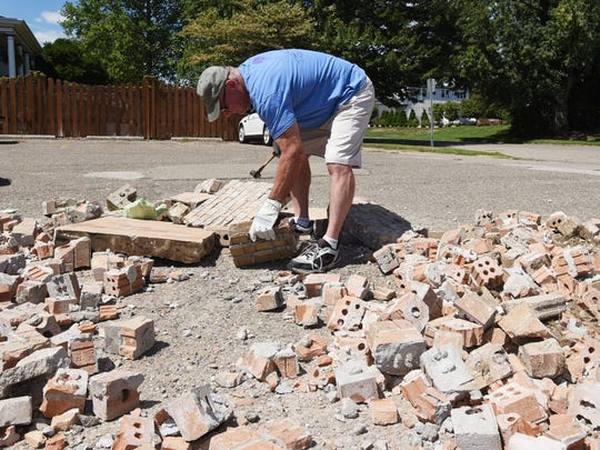 Kevin DeMent breaks up some bricks from the former Good Samaritan Hospital on Tuesday.