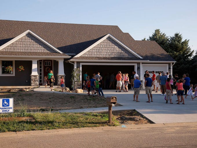 Guests gather outside at an open house for Lane and