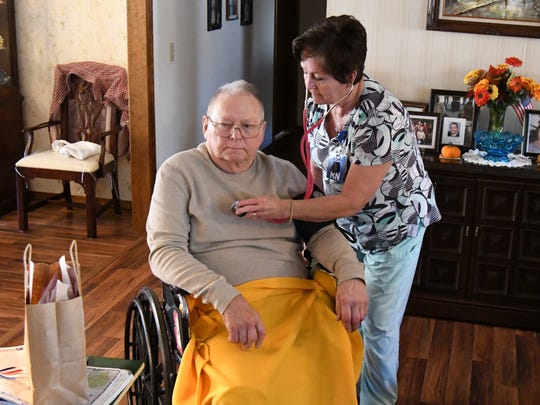 Registered Nurse Wanda Bollinger (standing) listens to the heart of Baxter Regional Home Health patient James Schad on Thursday.
