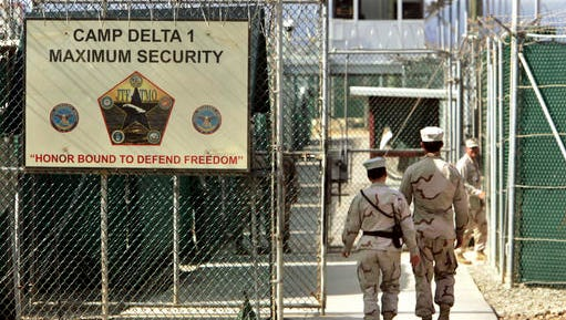 "FILE - In this June 27, 2006 file photo, reviewed by a US Department of Defense official, US military guards walk within Camp Delta military-run prison, at the Guantanamo Bay US Naval Base, Cuba. A draft executive order shows President Donald Trump asking for a review of America's methods for interrogation terror suspects and whether the U.S. should reopen CIA-run ""black site"" prisons outside the U.S."