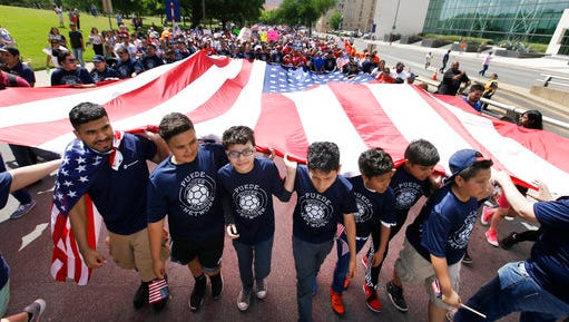 Youths and adults carry an American flag during a protest march through downtown Dallas, Sunday, April 9, 2017. Thousands of people are marching and rallying in downtown Dallas to call for an overhaul of the nation's immigration system and end to what organizers say is an aggressive deportation policy. (AP Photo/LM Otero)