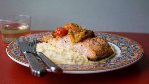 This February 2017 photo shows salmon with polenta and warm tomato vinaigrette in New York. This dish is from a recipe by Katie Workman.
