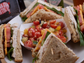 A sandwich with a Tomato & Blues salad featuring grape