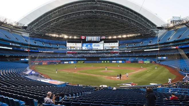 Photographers cover an intrasquad game in an empty stadium in Toronto on Friday.