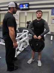 Andy Albertson works out under the supervision of his trainer, Jerry Hughes, left, at the Bill Bartley YMCA. Albertson, 22, weighs 145 pounds after reaching a high of 317 pounds two years ago.