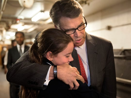 Rick Perry embraces Madeline Martin, daughter of Eagle Forum president Ed Mark, before speaking at the Eagle Council on Sept. 11, 2015.