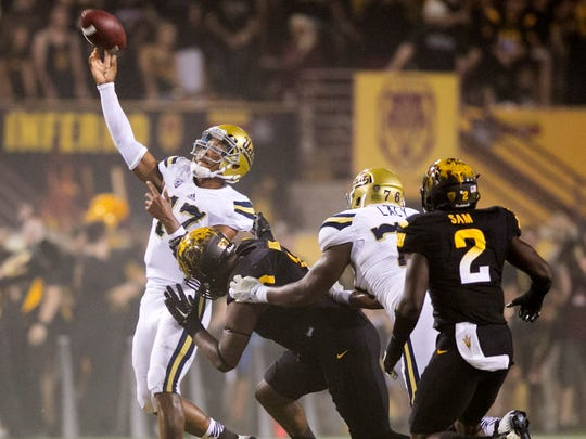 UCLA quarterback Brett Hundley throws the abll downfield as ASU defensive end Marcus Hardison applies pressure during the second quarter on Thursday, Sept. 25, 2014, at Sun Devil Stadium in Tempe.