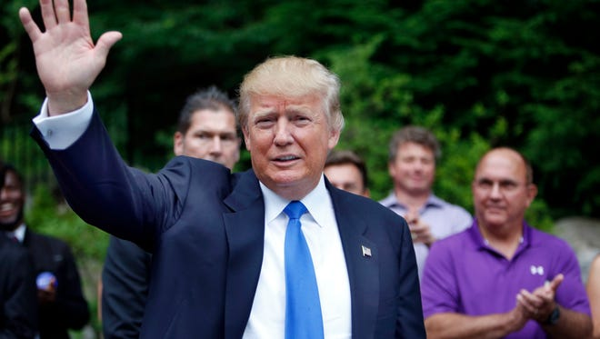 Republican presidential candidate Donald Trump waves as he arrives at a party Tuesday, June 30, 2015, in Bedford, N.H.