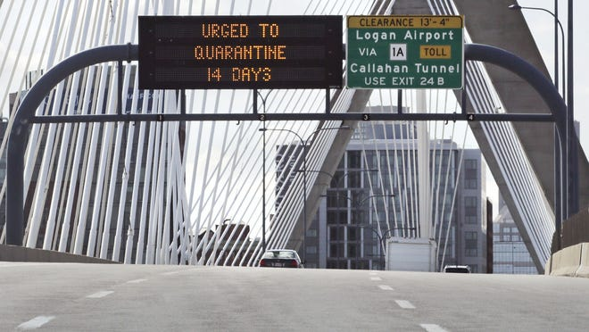 A few cars pass under a sign on the Zakim Bridge into Downtown Boston urging out of state visitors to quarantine for 14 days. The advisory will become mandatory on Aug. 1 in Massachusetts.