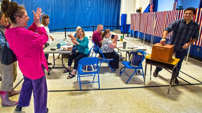 Sonam Friedensohn, right, gets a round of applause as he casts his first ballot while voting on the school budget at the Westford Elementary School on Tuesday.