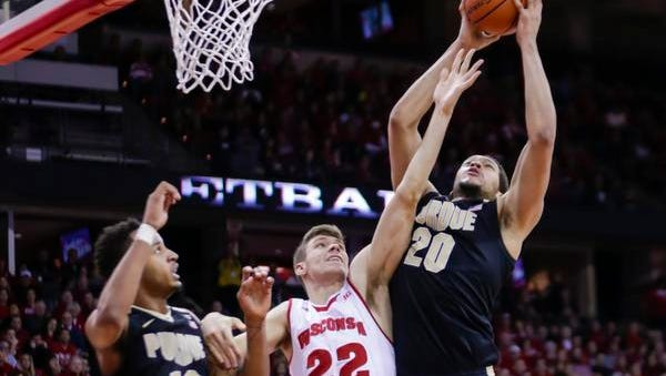 Purdue's A.J. Hammons (20) grabs a defensive rebound against Wisconsin's Ethan Happ (22) during the second half of an NCAA college basketball game Tuesday, Dec. 29, 2015, in Madison, Wis. At left is Purdue's Vince Edwards (12). (AP Photo/Andy Manis)