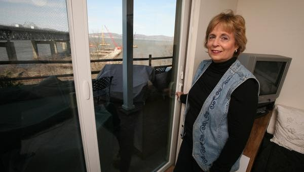 Alice Goldberg, the president of the board of managers at The Quay of Tarrytown condominiums, stands next to a new glass sliding door installed in her unit, photographed March 26, 2014. The new windows and doors will help minimize construction noise, as the new Tappan Zee Bridge is built. Her unit is serving as a prototype for the rest of the complex.
