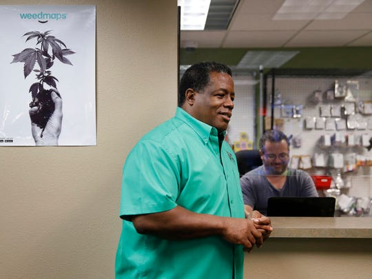 In this Sept. 8, 2017, photo, Frank Hawkins speaks with employees at the Nevada Wellness Center marijuana dispensary in Las Vegas. The former running back for the Raiders has two things that set him apart from most football players, a Super Bowl ring and a thriving pot shop just off the glittering Las Vegas Strip.