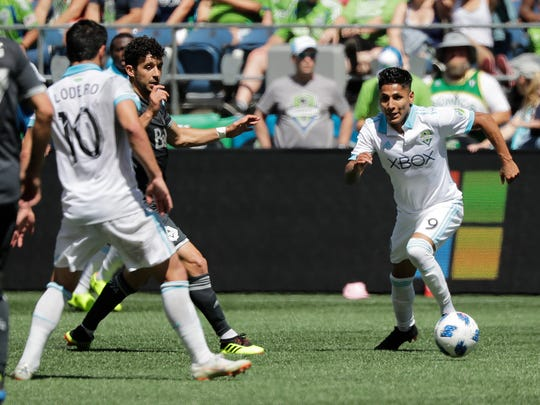 Seattle Sounders forward Raul Ruidiaz, right, moves on the ball during the second half of the team's MLS soccer match against the Vancouver Whitecaps, Saturday, July 21, 2018, in Seattle. The Sounders won 2-0. (AP Photo/Ted S. Warren)