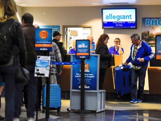 Passengers check in for an Allegiant flight to Florida