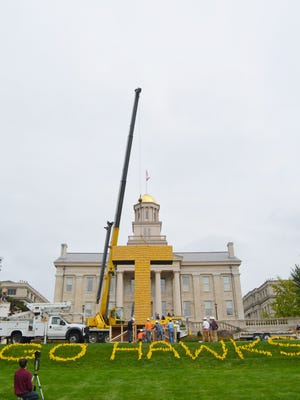 """A construction crew uses a crane to erect a corn tower in the shape of an 'I"""" on Monday on the University of Iowa's Pentacrest. The corn tower tradition is said to have started at UI in the 1910s."""