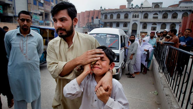 A man helps an injured boy to a hospital after an earthquake hit Peshawar, Pakistan, on Sunday.