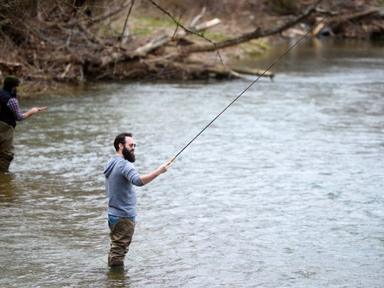 Jason Konopinski, left, and David Magbee use tenkara rods, which average 12-feet in length, to fish on a Saturday in March.