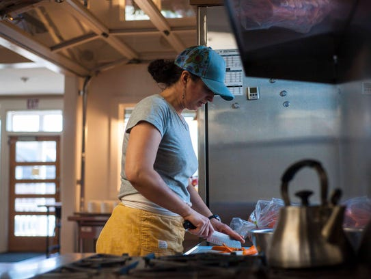 Amy Gifford chops carrots as she does prep work at