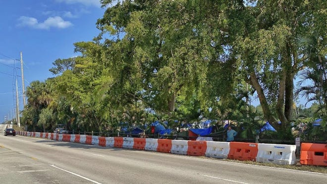 Orange barricades were erected Wednesday along Sixth Avenue South next to the homeless encampment at John Prince Park west of Lake Worth Beach.