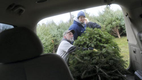 Scott Eberly, left, and Matt Wierl, Prospect Hill Cemetery workers, load a Christmas tree into a veteran's vehicle in this photograph from December 2014.