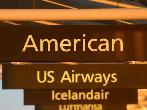American Airlines and US Airways signs stand next to each others at Denver International Airport. The two airlines have merged and announced new customer benefits.