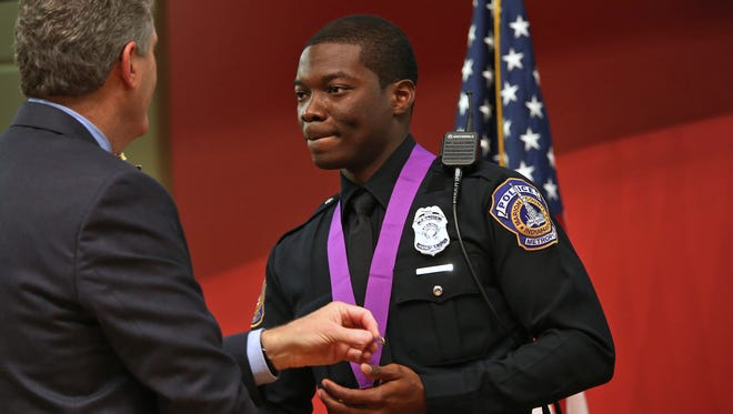 Officer Javed Richards, right, receives the Purple Heart from Interim Director of Public Safety David Wantz, left, and Chief of Police Rick Hite, not pictured, during the IMPD Honor Awards Program, Thursday, Nov. 5, 2015.