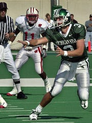 MSU quarterback Ryan Van Dyke pitches the ball as Wisconsin's Devery Hughes (11) looks on duirng first quarter action Saturday.