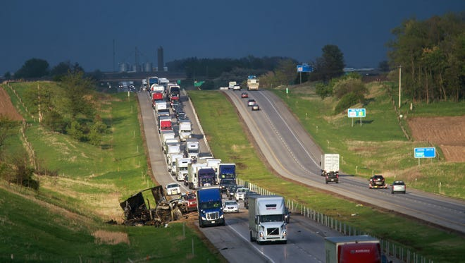 Traffic slows down as trucks past the wreckage of a multi-car accident on Interstate 80 west of Williamsburg on Friday, May 8, 2015. The accident started after a semi and several other vehicles caught fire in a pileup. There were no fatalities.