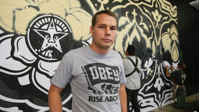 Artist Shepard Fairey works on a mural in the Belt alley in Detroit on May 16, 2015.