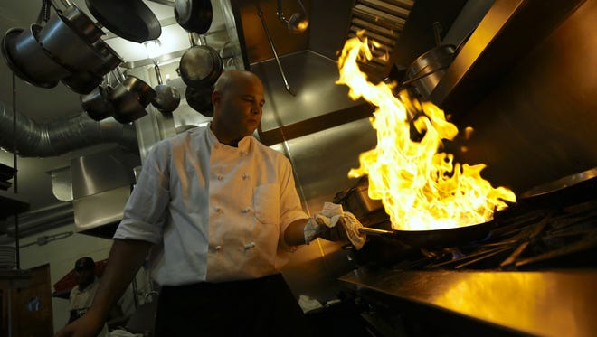 Chef Jestin Feggan works on the grill during the Detroit Free Press' Top 10 Takeover dinner series at the Antietam in Eastern Market, Detroit on Monday, July 13, 2015.