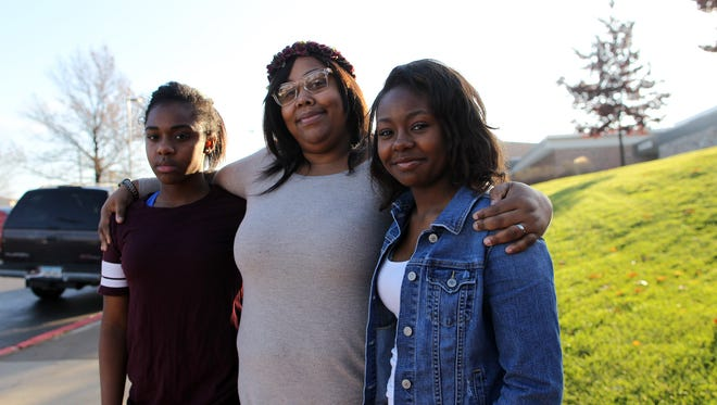 Kayahzah Hicks, left, poses with her mother, Zee Brown, and sister, Aahnevia Brown, outside West High on Tuesday, Dec. 1, 2015. Hicks enrolled in the LADDERS program to avoid criminal charges after a fight at school, though she was still suspended for five days.