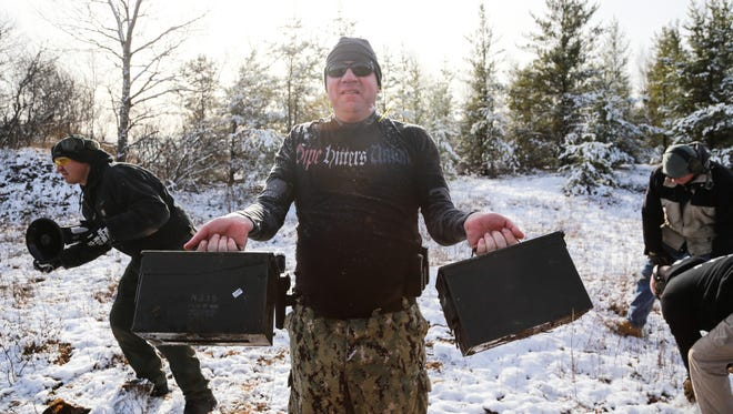 War Club prospect U.S. Navy veteran Will Kooy, of Skandia, 38, lifts ammo crates full of weight as the sounds of a blaring megaphone held by War Club public affairs officer Jason Hubble (left), of Manistique ring and snow is gathered to be thrown into his face by Damian Salmond (background right), 26, Marquette and War Club President Louis Cote, 32 of Marquette before being involved in a tactile training exercise firing live rounds as part of training for the War Club at a field outside of Marquette in Michigan's Upper Peninsula on Saturday November 14, 2015.