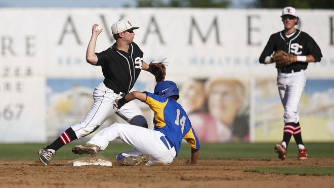 Santiam Christian's Tanner Macal throws to first after tagging out Stanfield-Echo's Antonio Flores in the OSAA 3A State Championship game on Friday, May 6, 2016 at the Volcanoes Stadium in Keizer. After ten innings, Stanfield-Echo won the title 5-4.