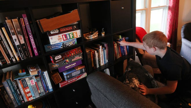 Ben Pierce, 7, picks out some of his favorite books and board games at his home on Wednesday, June 22, 2016. Ben was diagnosed with generalized anxiety disorder and attention deficit and hyperactivity disorder. His 9-year-old sister, Ela, was diagnosed with autism, disruptive behavior disorder, generalized anxiety disorder and attention deficit and hyperactivity disorder.