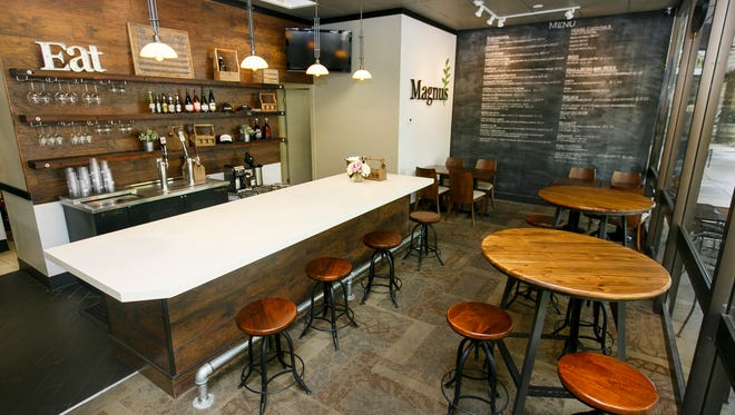 Magnus has a variety of seating options, including high-top tables and barstools. The shop serves breakfast options and internationally inspired sandwiches, as well as classic cocktails and local brews.