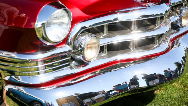 Spectators are reflected in the fender of a 1950 Cadillac Convertible at the 26th annual Carousel Cruise on Saturday, Sept. 2, 2017, in Salem's Riverfront Park. Over 225 cars showed up to the event, which is hosted by Willamette Valley Street Rods.