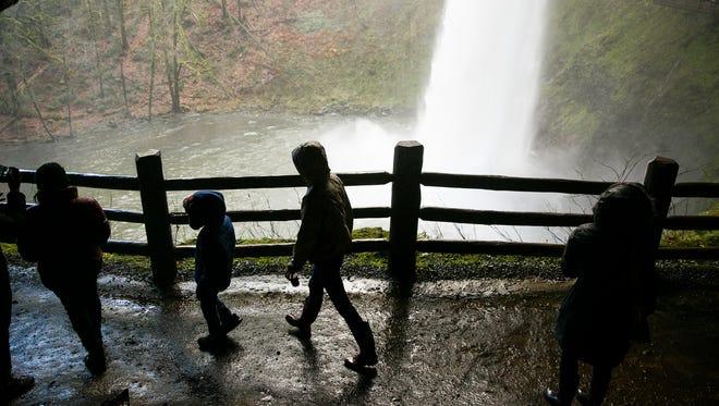 Visitors at Silver Falls State Park walk behind South Falls in November.