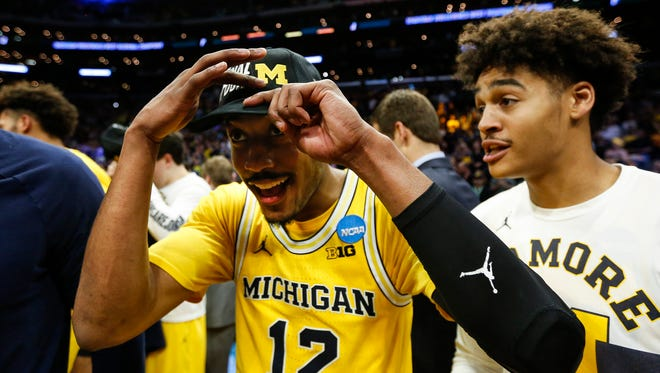 Muhammad-Ali Abdur-Rahkman celebrates and puts on the Final Four hat next to guard Jordan Poole after Michigan won the West Region of the NCAA tournament over Florida State in Los Angeles, Saturday, March 24, 2018.