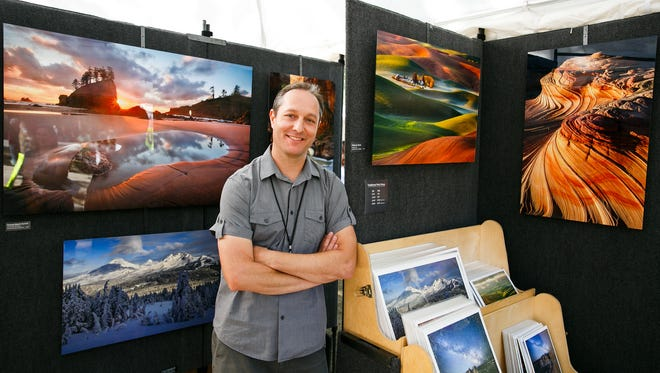 Zach Schnepf of Bend stands with some of his photographs at the Salem Art Fair on Friday, July 20, 2018, in Bush's Pasture Park. Many of Schnepf's images are printed on aluminum, giving them a vibrant, glossy appearance.