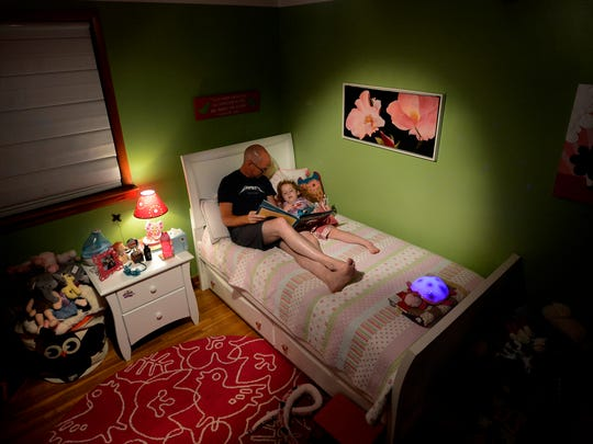 Mark reads a book to Maggie before bed Tuesday, June 7, 2016, in Pegram, Tenn. Joanna Montgomery, Mark's wife, died from cancer at the age of 47.