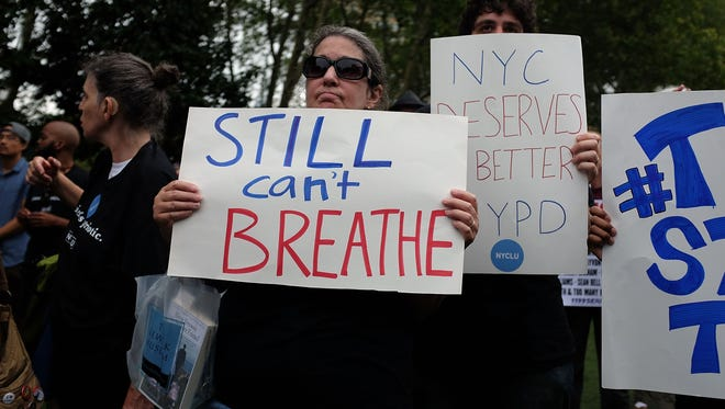 People attend a rally in Brooklyn to call for justice for Eric Garner one year after he died in an apparent police chokehold on July 18, 2015 in New York City.
