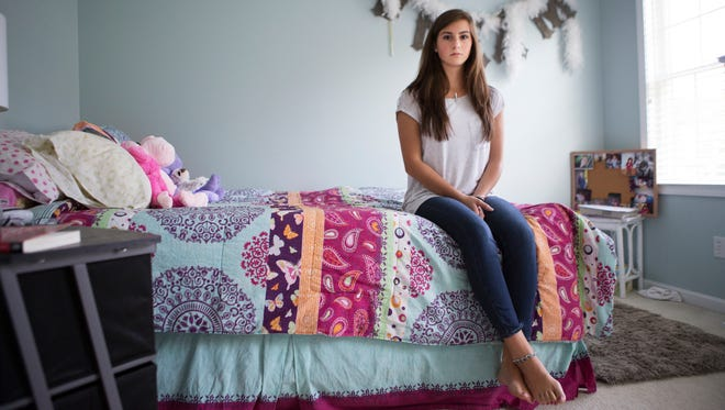 Brigid Lawler, 17, sits in her bedroom at her home in Victor on Aug. 16, 2015. Brigid was the employee at Tri Running & Walking who realized the owner, Glen Siembor, was filming girls in the changing room.
