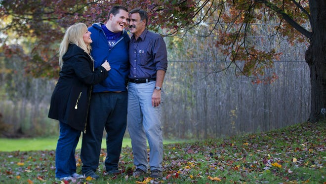 Sherry and Mike Battisti of Ogden stand with their son, Anthony, on the land where they plan to build a home for young adults with autism on Hinchey Road in Gates.