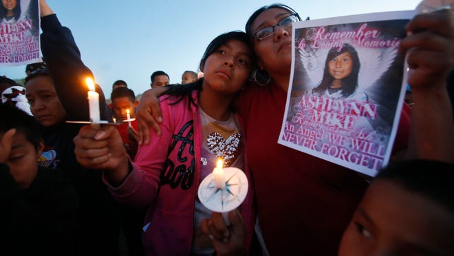 In this May 4, 2016, photo, Klandre Willie, left, and her mother, Jaycelyn Blackie, participate in a candlelight vigil for Ashlynne Mike at the San Juan Chapter House in Lower Fruitland, N.M. The FBI said Ashlynne was abducted after school and her body was found the next day. The death of the young Navajo Nation girl is fueling efforts to create an Amber Alert plan on the vast reservation.