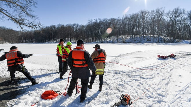 Henderson City firefighters use a rope to help pull firefighter Cory Agnew and assistant chief Chad Moore out of a hole in the icy lake at Audubon State Park during an ice rescue training session Thursday.
