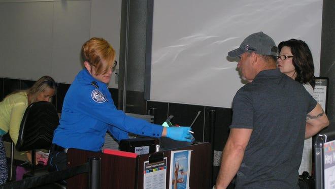 Melissa Hansen, transportation security officer for TSA, checks in passengers Wednesday at Austin Straubel International Airport in Ashwaubenon. TSA is launching its PreCheck expedited screening program at the airport.