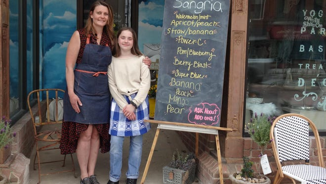 Dori Heck and her daughter, Lily, stand out front of the Sangria Stand in downtown Massillon. Heck has been selling her signature sangrias sealed in mason jars to go as a curbside service during the pandemic shut down.