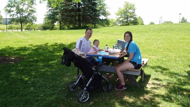 The Reed family from Uniontown take time out to enjoy time together with a picnic in Jackson Township's North Park. From left, Ryan, Jocelyn and baby Addilyn.
